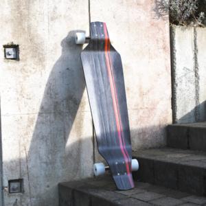 Longboard, schwarz mit rotem Zierstreifen, auf einer Treppe im Sonnenschein an eine Betonwand lehnend.